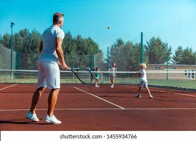 Family loving sport. Happy family loving sport feeling amazing while playing tennis at the weekend