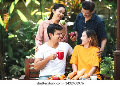 Family lunch outdoor. Married mix race couple with grand parents. White man, Asian pregnant woman with senior asian couple in tropical garden. Talking to eath other, laughing.