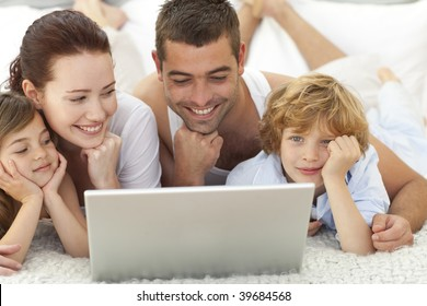 Family lying in bed playing with a laptop