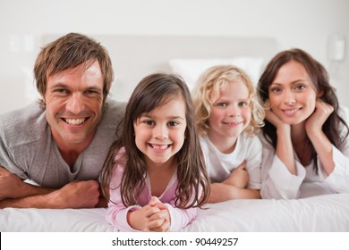 Family lying in a bed together