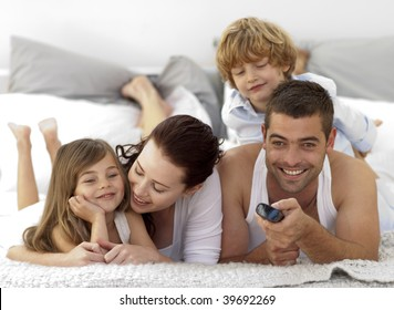 Family lying in bed watching television and using a remote