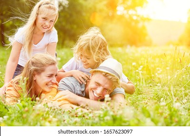 Family is lying in a meadow during their summer vacation