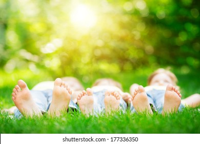 Family lying on green grass in spring park. Healthy lifestyle concept