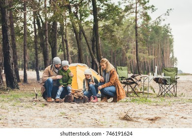 family making campfire together while having trip on autumn day