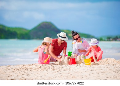 Family making sand castle on white beach. Parents and kids playing together on summer holidays