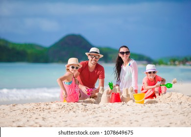 Family making sand castle at tropical beach