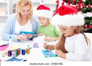 Family making seasonal greeting cards together at christmas time