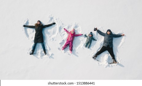 Family making a snow angel. Aerial view. Mother and father and chilren making a snow angel