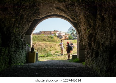 Family male and female doing outdoor urban exploration in a city of Albania Eastern Europe seen from inside ancient brick tunnel.
