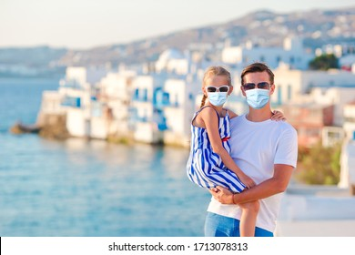 Family of man and little girl wearing masks for prevent virus background famous little Venice in Mykonos. Protection against Coronavirus and gripp