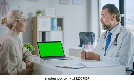 Family Medical Doctor is Explaining Diagnosis to a Senior Patient on a Computer with Green Screen in a Health Clinic. Assistant in White Lab Coat is Reading Medical History in Hospital Office.