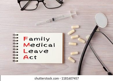 Family And Medical Leave Act (FMLA) written on notebook with stethoscope, syringe and pills. Medical concept.