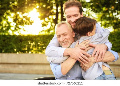 Family meeting. A man and a boy came to see his grandfather, who is sitting in a park on a wheelchair. The old man, his son and grandson embrace, they are happy