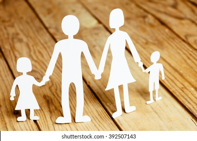 Family members paper dolls on a wooden background.
