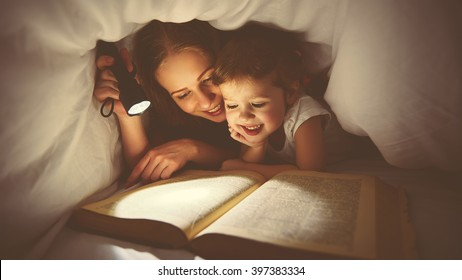 Family   Mom and child daughter reading a book with a flashlight under the blanket in bed