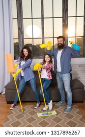 Family mom dad and daughter with cleaning supplies at living room. We love cleanliness and tidiness. Cleaning together easier and more fun. Family care about cleanliness. Start cleaning. Cleaning day.