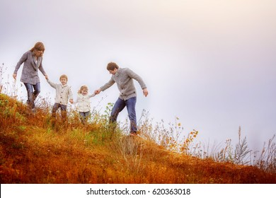 Family mom, dad, son and daughter go down the hill, overgrown with a withered autumn tar. A man helps his children safely go downstairs