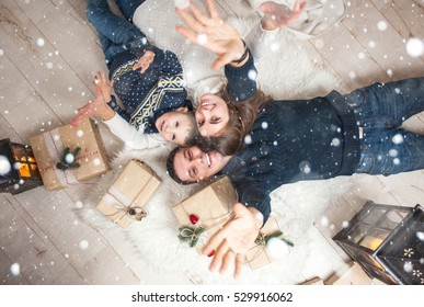 Family, mom, dad, son and are looking up, laughing, and pleased, to catch the snow on Christmas Eve/Family portrait