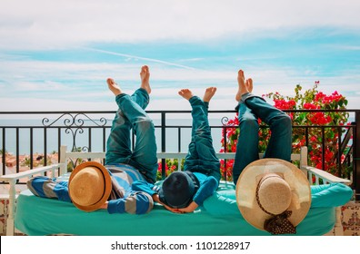 family- mom, dad and son- relax on balcony terrace