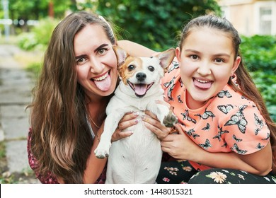 family mom and daughter with dog jack russel in summer in the yard
