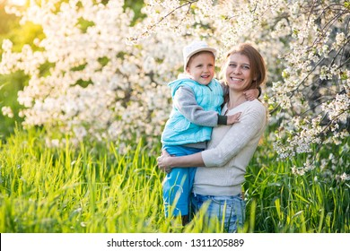 Family mom with daughter girl woman with child in spring stand and hug under blossoming tree