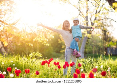 Family mom with daughter woman with child in spring stand and hug on a glade with green grass and tulips at sunset