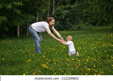 Family. Mom and son are walking around meadow holding hands. Pregnant girl helps little boy learn to walk. Yellow dandelions grow in meadow.
