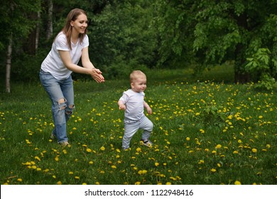 Family. Mom and son are walking around meadow holding hands. Pregnant girl is happy. Little boy learn to walk. Yellow dandelions grow in meadow.