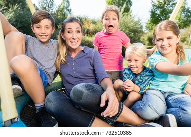 Family with mom, sons and daughters taking photo together outdoors