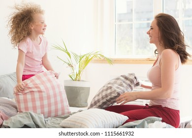 Family morning. Daughter with curly and mother on bed in bedroom. They fool around and arrange pillow fight. Happy childhood and parenthood