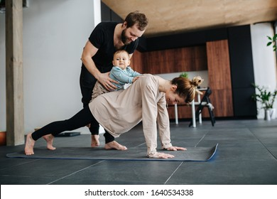 Family morning exercise. Mother doing plank, father holding their baby on her back, so he would ride her, including child in activity.