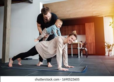 Familienmorgenübung. Mutter, die plank, Vater hielt ihr Baby auf dem Rücken, sodass er sie reiten würde, einschließlich Kind in Aktivität. Familiendomizil, häusliches Leben in Selbstisolierung. Sonnenlicht