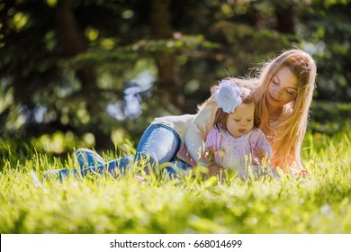 Family, mother and baby girl resting on nature, lying on grass