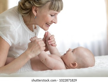 Family mother and baby playing and laughing