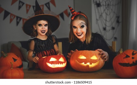 family mother and child daughter in costumes and makeup to halloween with pumpkin in   dark at home