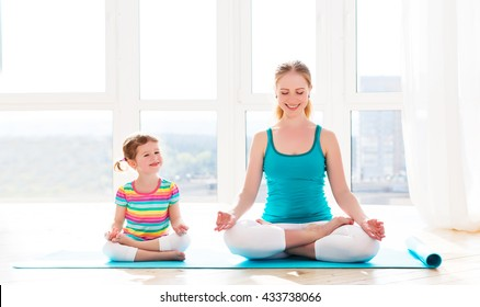family mother and child daughter are engaged in meditation and yoga, exercise at home