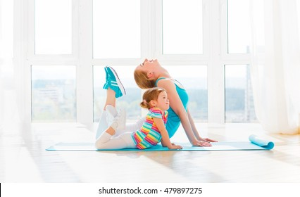 family mother and child daughter are engaged in fitness, yoga, exercise at home