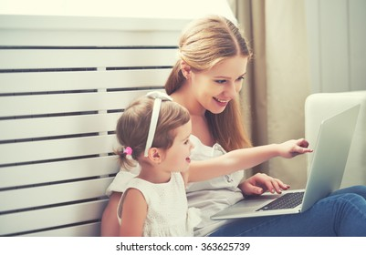 family mother and child daughter at home with a laptop