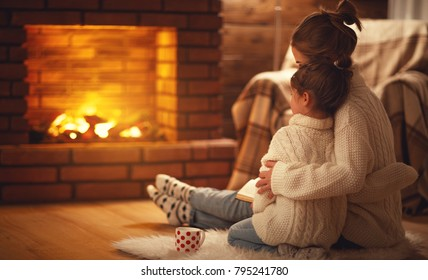 family mother and child daughter hugs and warm on winter evening by fireplace