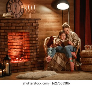 family mother and child daughter reading book and drink tea on winter evening by fireplace
