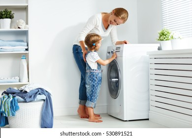 family mother and child girl little helper in laundry room near washing machine and dirty clothes