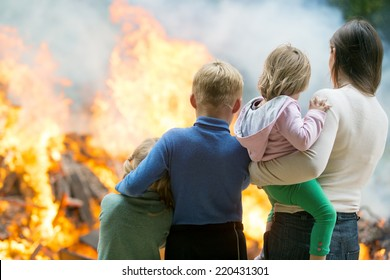 Family mother with children at burning house fire accident background