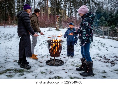 Family with mother and children at a campfire grilling hot dog food. Winter snow outdoor scene.