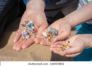 Family of mother and children holding and showing small tiny harmful plastic microbeads collected on the beach in Zante, Zakynthos, Greece