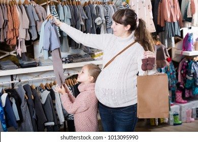 Family mother and daughter hiking in a clothing store for babies