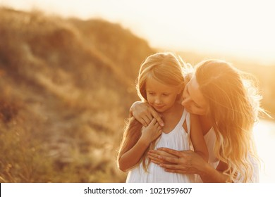 Family, mother and daughter on the river bank. The girl bends over and says something to her daughter. Girls in white dresses. They are blondes. Family time together.