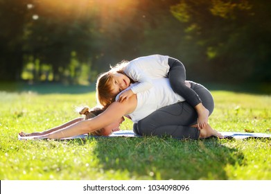 Family of mother and daughter practicing yoga child pose together in the park
