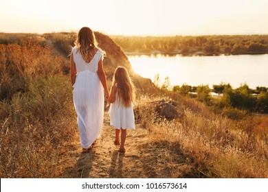 Family, mother and daughter are walking along the river bank. Little girl and mother holding hands. Girls in white dresses. They are blondes. Family time together.