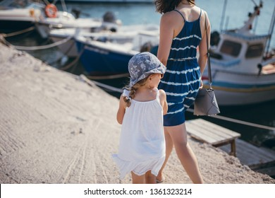 Family of mother and daughter walking on the embankment, daughter looking over the shoulder