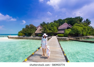 Family mother and daughter in white dress and hat walking on wooden deck near the beach enjoying tropical summer vacation. Background of a water bungalow, beauty of the sea with the coral reefs
